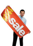 Business or salesman holding Sale Banner. A happy excited businessman, salesman or storeperson holding a vinyl sale banner sign ready to hang royalty free stock photo