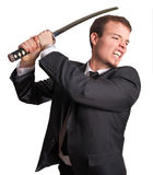 Business samurai. Young business man attacking with a katana isolated Royalty Free Stock Images