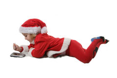 Business Santa helper with PDA. Cute little elf play with PDA Royalty Free Stock Photos