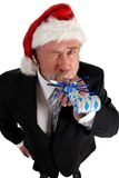 Business Santa noise maker. Business man in santa hat blowing party blower Stock Photography