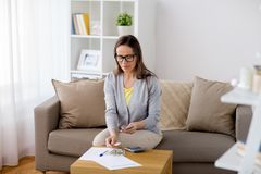 Woman with papers counting money at home Stock Image