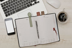 Business scene with diary, laptop and cell. Some business accessories - diary with funny bookmarks, laptop with a mouse, cell phone and a cup of coffee on wooden royalty free stock photography