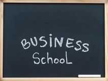 Business school message written with white chalk on wooden frame blackboard, available copy space above Royalty Free Stock Photography
