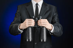 Business and search topic: Man in black suit holding a black binoculars in hand on a dark blue background in studio isolated Stock Image