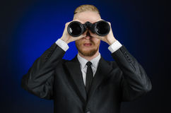 Business and search topic: Man in black suit holding a black binoculars in hand on a dark blue background in studio isolated. Business and search topic: Man in stock images