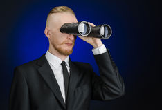 Business and search topic: Man in black suit holding a black binoculars in hand on a dark blue background in studio isolated Royalty Free Stock Photo