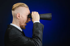 Business and search topic: Man in black suit holding a black binoculars in hand on a dark blue background in studio isolated Stock Photography