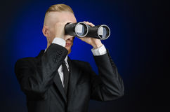 Business and search topic: Man in black suit holding a black binoculars in hand on a dark blue background in studio isolated Stock Photo