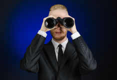 Business and search topic: Man in black suit holding a black binoculars in hand on a dark blue background in studio isolated Stock Images