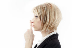 Business secret. Corporate secret business concept with businesswoman with finger to lips for quiet or keeping secret royalty free stock photography
