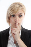 Business secret. Corporate secret business concept with businesswoman with finger to lips for quiet or keeping secret royalty free stock photo