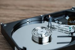IT business security or big data concept with miniature business. Man thinking and standing on read and write arm of hard drive platter Royalty Free Stock Photos