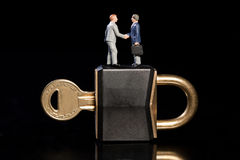 Business Security Horizontal. Two toy model miniature businessmen shake hands standing on top of a padlock and key, conceptual od business security Stock Image