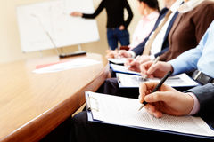 Business seminar. Close-up of businesspeople hands holding pens and papers near table at business seminar