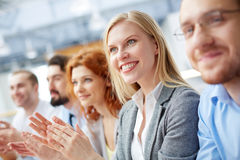 Business seminar. Closeup image of a smiley business leader clapping at the seminar with her team on the foreground royalty free stock image