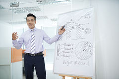 Business seminar. Young businessman explaining business strategy during seminar Stock Photography