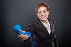 Business senior lady handing   big blue telephone receiver. Business senior lady handing  big blue telephone receiver on black background with copyspace Stock Photo