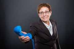 Business senior lady handing   big blue telephone receiver. Business senior lady handing  big blue telephone receiver on black background with copyspace Royalty Free Stock Photo