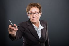 Business senior lady handing screwdriver. On black background Royalty Free Stock Photo