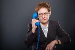 Business senior lady holding   blue telephone receiver making la. Business senior lady holding  blue telephone receiver making late gesture on black background Royalty Free Stock Photos