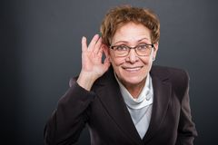 Business senior lady showing cant hear you gesture. On black background with copyspace advertising area royalty free stock images