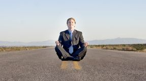 Business serenity. Business man meditates while waiting along a deserted highway Royalty Free Stock Photos