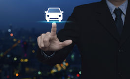 Business service car concept. Businessman pressing car flat icon over blur colorful night light city tower, Business transportation service concept Royalty Free Stock Photo