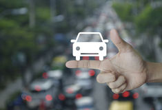 Business service car concept. Car flat icon on finger over blur of rush hour with cars and road, Business service car concept Stock Photo