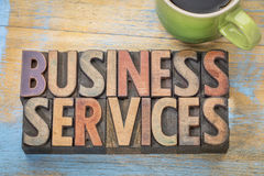 Business services in wood type. Business services word abstract in letterpress wood type blocks with a cup of coffee stock photos