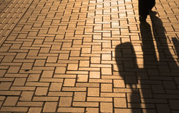 Business shadows. Sunset pavement reflections of a walking businessman with bag Royalty Free Stock Photo