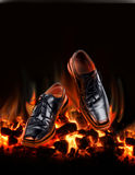 Business shoes dancing over fire Royalty Free Stock Image