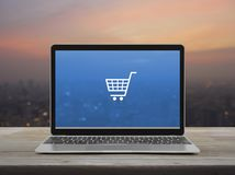 Business shop online concept. Shopping cart flat icon with modern laptop computer on wooden table over blur of cityscape on warm light sundown, Business shop royalty free stock image