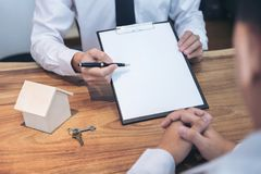 Business Signing a Contract Buy - sell house, insurance agent an. Alyzing about home investment loan Real Estate concept Royalty Free Stock Photo