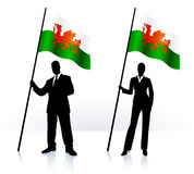 Business silhouettes with waving flag of Wales Stock Image