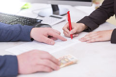 Business situation. Busineswoman signing loan contract,with money, Euro banknotes on Royalty Free Stock Photos
