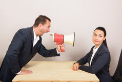 Business situation, humorous concept. Man shouts through a megaphone at the woman, but she ignores him Stock Image