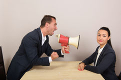 Business situation, humorous concept. Man shouts through a megaphone at the woman, but she ignores him Royalty Free Stock Photography