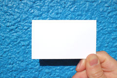 Business sized white card and the blue wall Royalty Free Stock Photo
