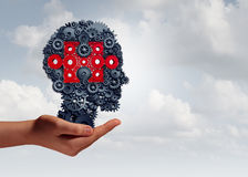 Business Skills Training. And corporate learning concept as a hand holding a group of gear and cog objects shaped as a human head with a jigsaw puzzle piece as Stock Photos