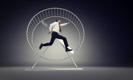 Business slave concept. Caucasian businessman run in abstract hamster wheele stock photos
