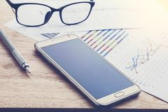 Business, smart phones and paper report on a wooden table. busin Royalty Free Stock Photos