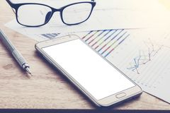 Business, smart phones and paper report on a wooden table. busin Stock Image