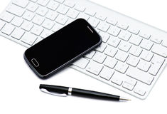 Business smartphone on the keyboard, with pen Royalty Free Stock Photography