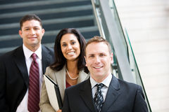 Business: Smiling Team Stands Together By Stairs Stock Photo