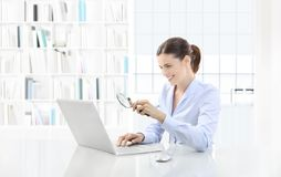Business smiling woman or a clerk working at her office desk wit Stock Image