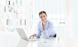 Business smiling woman or a clerk working at her office desk wit Royalty Free Stock Images