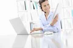 Business smiling woman or a clerk working at her office desk wit Royalty Free Stock Image