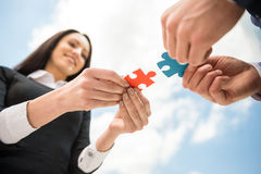 Business solution. Closeup of business people wanting to put two pieces of puzzle together. Sky background Royalty Free Stock Image