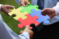 Business solution. Teamwork concept, four business people holding jigsaw puzzle pieces together Royalty Free Stock Image