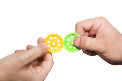 Business solutions, assistance and teamwork. Two hands holding colorful gears and support, complete each other Stock Photos